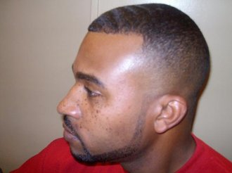 A black male with a fresh fade haircut